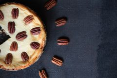 Cheesecake with pecan nuts on a black background Royalty Free Stock Images