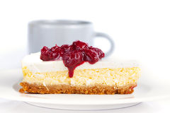 Cheesecake on a plate and coffee cup on a table Royalty Free Stock Image