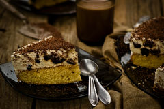 Cheesecake with prunes and chocolate cut on pieces Stock Images