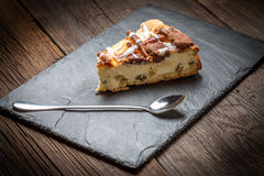 Cheesecake with raisins on a slate plate. Royalty Free Stock Photography