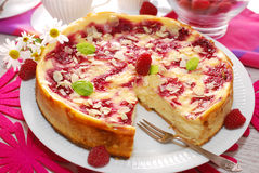 Cheesecake with raspberries and almonds. Round cheesecake with rasperries and almond flakes on party table Royalty Free Stock Photo