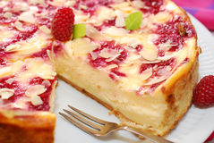 Cheesecake with raspberries and almonds. Round cheesecake with rasperries and almond flakes on party table Royalty Free Stock Images