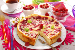 Cheesecake with raspberries and almonds. Round cheesecake with rasperries and almond flakes on party table Stock Photography
