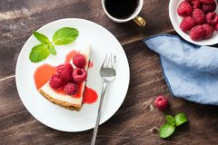 Cheesecake with raspberries and berry sauce on wooden table. Top view, selective focus Royalty Free Stock Images