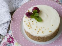 Cheesecake with raspberries and mint on a pink plate on a wooden table with floral fabric and laces. Close up, copy space royalty free stock photo