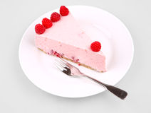 Cheesecake with raspberry. With fork on a white plate Royalty Free Stock Photo
