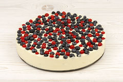 Cheesecake with  red currants and  blueberries  on the wooden background. Cheesecake with  red currants and  blueberries  on the white wooden background Royalty Free Stock Photography