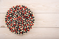 Cheesecake with red currants and blueberries on the wooden background. Cheesecake with red currants and blueberries on the white  wooden background Stock Images