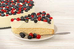 Cheesecake with  red currants and  blueberries  on the wooden background. Cheesecake with  red currants and  blueberries  on the white wooden background Stock Image