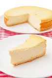 Cheesecake slice. On dish with full pie in background Stock Images