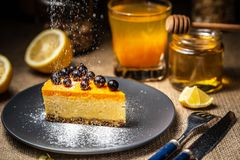 Cheesecake slice on a blue plate. Sugar snow. Sugar snow stock image