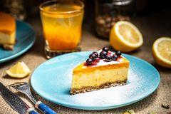 Cheesecake slice on a blue plate. Sugar snow stock image