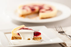 Cheesecake Slice and Cream. Cheesecake slice with cherry jam decoration on a plate with fork and cheesecake in the background. Cream poured over Stock Photo