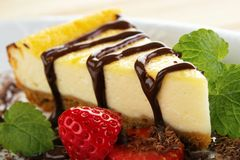Cheesecake slice. And melted chocolate with strawberry Royalty Free Stock Photo