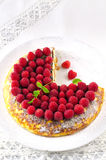 Cheesecake, souffle, cream mousse, pudding dessert with fresh raspberries and mint leaves on a white plate.  Royalty Free Stock Image