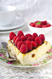 Cheesecake, souffle, cream mousse, pudding dessert with fresh raspberries and mint leaves on a white plate.  Royalty Free Stock Images