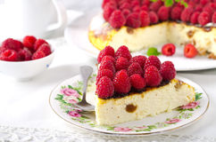 Cheesecake, souffle, cream mousse, pudding dessert with fresh raspberries and mint leaves on a white plate.  Stock Photos