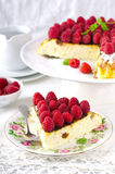 Cheesecake, souffle, cream mousse, pudding dessert with fresh raspberries and mint leaves on a white plate.  Stock Photography