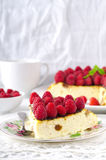 Cheesecake, souffle, cream mousse, pudding dessert with fresh raspberries and mint leaves on a white plate.  Royalty Free Stock Photography
