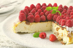 Cheesecake, souffle, cream mousse, pudding dessert with fresh raspberries and mint leaves on a white plate. Toned Stock Photography