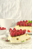 Cheesecake, souffle, cream mousse, pudding dessert with fresh raspberries and mint leaves on a white plate Stock Photos