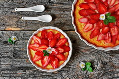 Cheesecake with strawberries and fresh flowers, strawberries on a wooden table. Left view Stock Photo