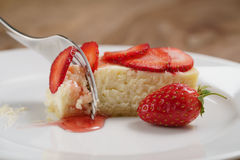 Cheesecake with strawberry on plate closeup eaten with fork Royalty Free Stock Images
