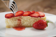 Cheesecake with strawberry on plate closeup eaten with fork Stock Photos