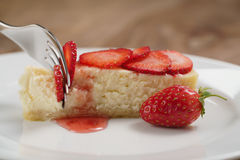 Cheesecake with strawberry on plate closeup eaten with fork Royalty Free Stock Photos