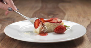 Cheesecake with strawberry on plate eaten with fork Royalty Free Stock Images