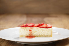 Cheesecake with strawberry on plate on wood table Royalty Free Stock Images