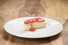 Cheesecake with strawberry on plate on wood table Royalty Free Stock Photo