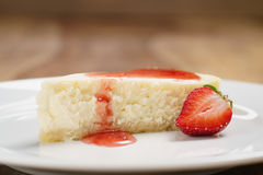 Cheesecake with strawberry on plate on wood table Royalty Free Stock Image