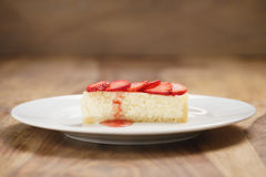 Cheesecake with strawberry on plate on wood table Stock Image