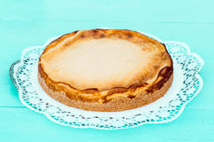 Cheesecake on a turquoise wood with cake lace Stock Photos