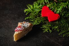 Cheesecake on Valentine`s Day with strawberry, kiwi hearts on fir and dark background stock images