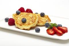 Cheesecakes από το τυρί εξοχικών σπιτιών με τα σμέουρα, τις φράουλες και τα βακκίνια στοκ εικόνες με δικαίωμα ελεύθερης χρήσης