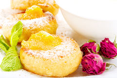 Cheesecakes σε ένα άσπρο πιάτο με την ξινή κρέμα Στοκ Φωτογραφία