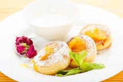Cheesecakes σε ένα άσπρο πιάτο με την ξινή κρέμα Στοκ φωτογραφίες με δικαίωμα ελεύθερης χρήσης