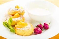 Cheesecakes σε ένα άσπρο πιάτο με την ξινή κρέμα Στοκ Φωτογραφίες