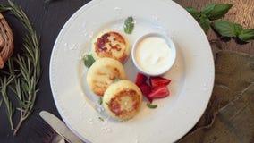 Cheesecakes του τυριού εξοχικών σπιτιών με τις φράουλες απόθεμα βίντεο