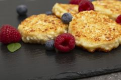 Cheesecakes from cottage cheese. Cottage cheese pancakes or curd fritters decorated fresh raspberries and blueberries. stock photo