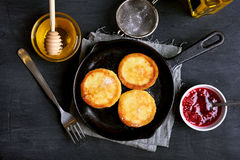 Cheesecakes, curd cheese pancakes. In frying pan on dark background, top view Royalty Free Stock Images