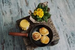 Cheesecakes in a frying pan , yellow flowers and jam Stock Photos
