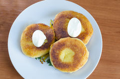 Cheesecakes. Grandma's curd pancakes with their hands with scented cream Stock Photos