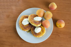 Cheesecakes. Grandma's curd pancakes with their hands with scented sour cream and sweet apricots Royalty Free Stock Image