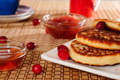 Cheesecakes with honey and jam. Serving breakfast. cheesecakes on a white plate. honey and jam with a glass bowl Royalty Free Stock Image