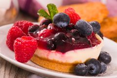 Cheesecakes with mixed berries. Cheesecakes with mixed berries on white dish royalty free stock photos