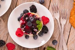 Cheesecakes with mixed berries. Cheesecakes with mixed berries on white dish stock photography