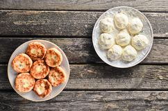 Cheesecakes on a wooden rustic table. Traditionally, Russian raw and fried pancakes with cottage cheese. The cooking process. Top view Stock Images